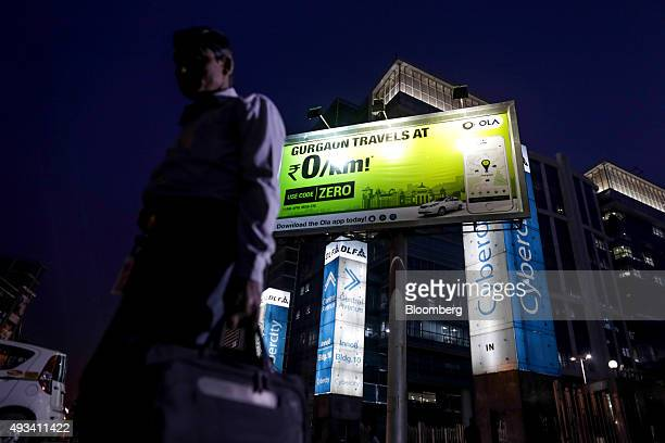 A pedestrian walks past an advertisement for the Ola ridehailing service and application owned by ANI Technologies Pvt in New Delhi India on Saturday...