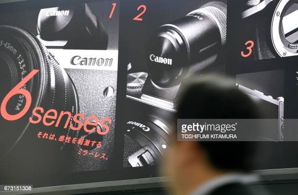 A pedestrian walks past an advertisement of Canon's latest mirrorless digital camera at a raiway station in Tokyo on April 26 2017 / AFP PHOTO /...