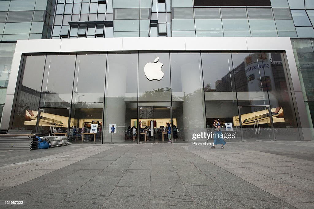 A pedestrian walks past an Apple Inc. store in Beijing, China, on Thursday, Aug. 25, 2011. Apple Inc. Chief Executive Officer Steve Jobs, who transformed the company he started at age 21 from a personal-computer also-ran into the world's largest technology company, resigned. Photographer: Nelson Ching/Bloomberg via Getty Images
