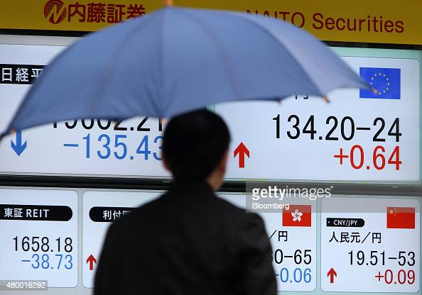 A pedestrian walks past an electronic board displaying exchange rates of the yen against the euro top right the Hong Kong dollar bottom second right...