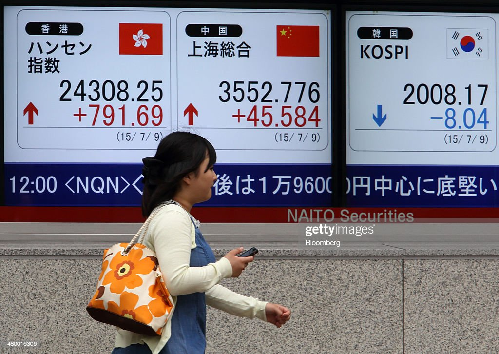 A pedestrian walks past an electronic board displaying the Hang Seng Index left the Shanghai Composite Index center and the Kospi index outside a...