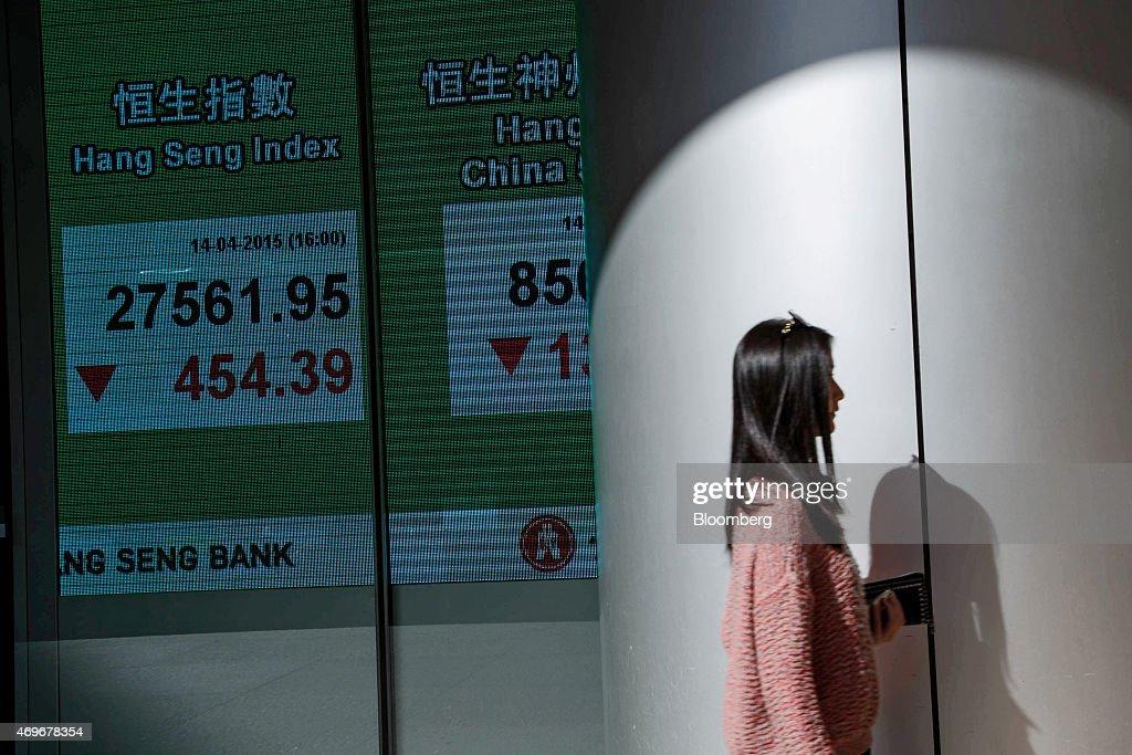 A pedestrian walks past an electronic display showing the closing figure of the Hang Seng Index at the Hang Seng Bank Ltd headquarters in Hong Kong...