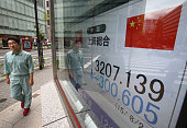 A pedestrian walks past an electronic stock board displaying the Shanghai Composite Index outside a securities firm in Tokyo Japan on Monday Aug 24...