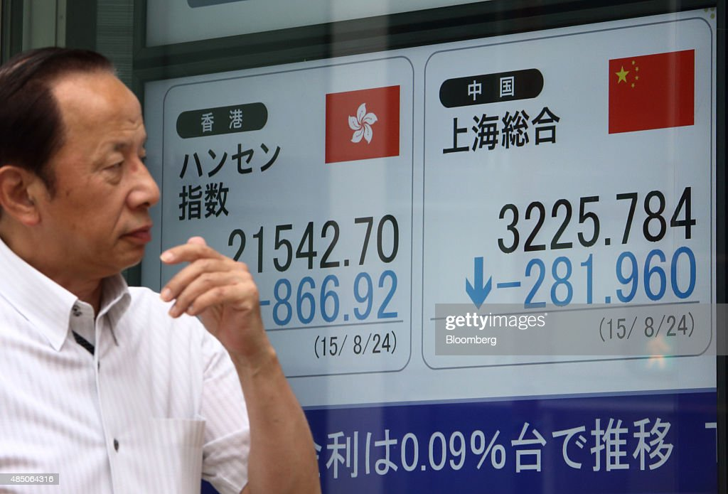 A pedestrian walks past an electronic stock board displaying the Hang Seng Index left and the Shanghai Composite Index outside a securities firm in...