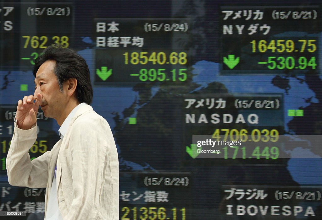 A pedestrian walks past an electronic stock board displaying the closing figures of the Nikkei 225 Stock Average center top outside a securities firm...