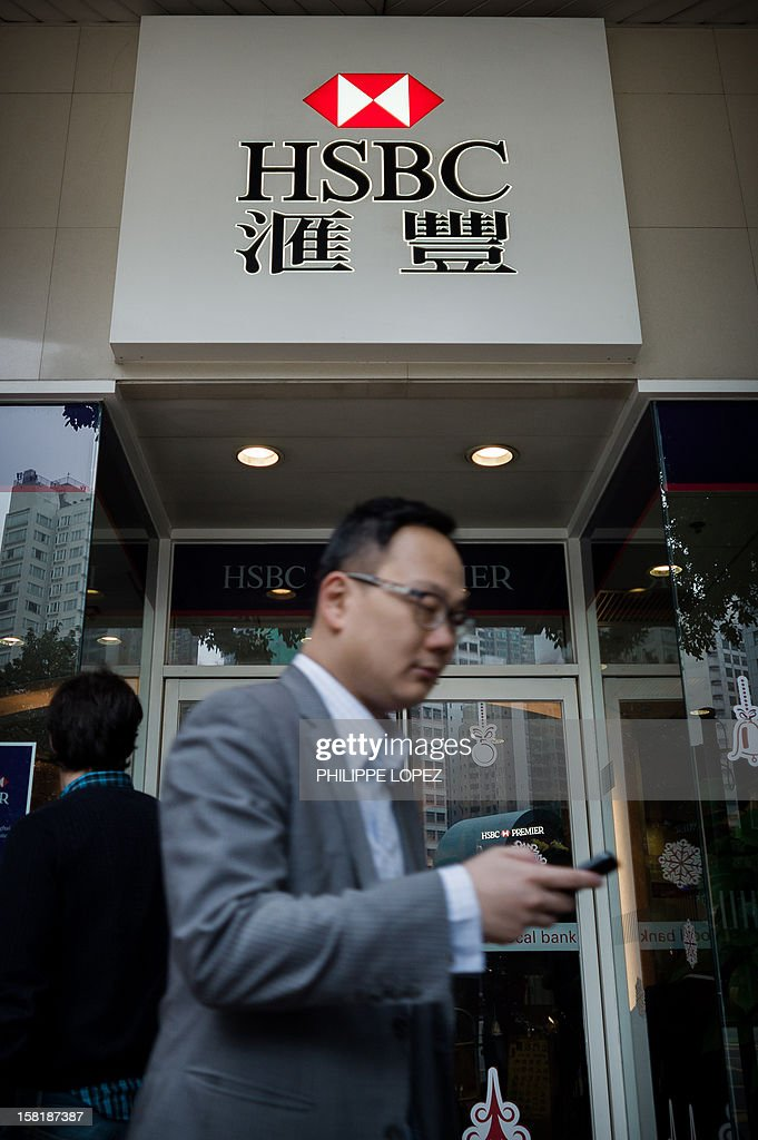 A pedestrian walks past an HSBC branch in Hong Kong on December 11, 2012. Banking giant HSBC said it had agreed to pay US authorities a record 1.92 billion USD to settle allegations of money laundering, as it said sorry again over its 'past mistakes'. AFP PHOTO / Philippe Lopez