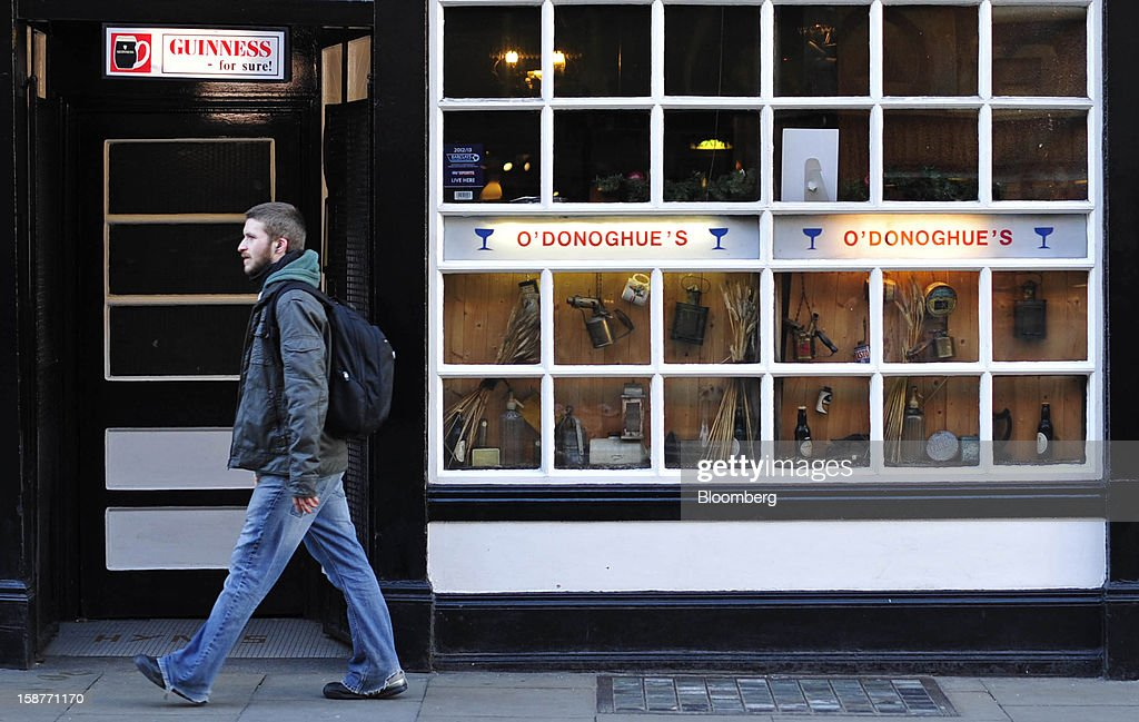A pedestrian walks past an Irish pub advertising the Guinness stout drink above the entrance in Dublin, Ireland, on Thursday, Dec. 27, 2012. Ireland will take over the EU presidency in January as the euro-area wrestles with putting the European Central Bank in charge of lenders within the currency union and other participating nations. Photographer: Aidan Crawley/Bloomberg via Getty Images