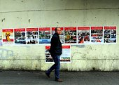 A pedestrian walks past antiterror propaganda posters pasted along the streets of Urumqi farwest China's Xinjiang region on September 16 2014 Ilham...
