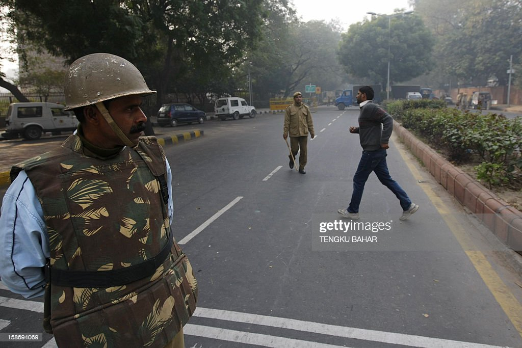 A pedestrian walks past as Indian policemen keep watch along a sealed-off road leading towards the landmark India Gate monument following weekend clashes between demonstrators and police in New Delhi on December 24, 2012. Indian Prime Minister Manmohan Singh has appealed for calm and vowed to protect women as police struggled to quell increasing outrage over sex crimes following the gang-rape of a student.