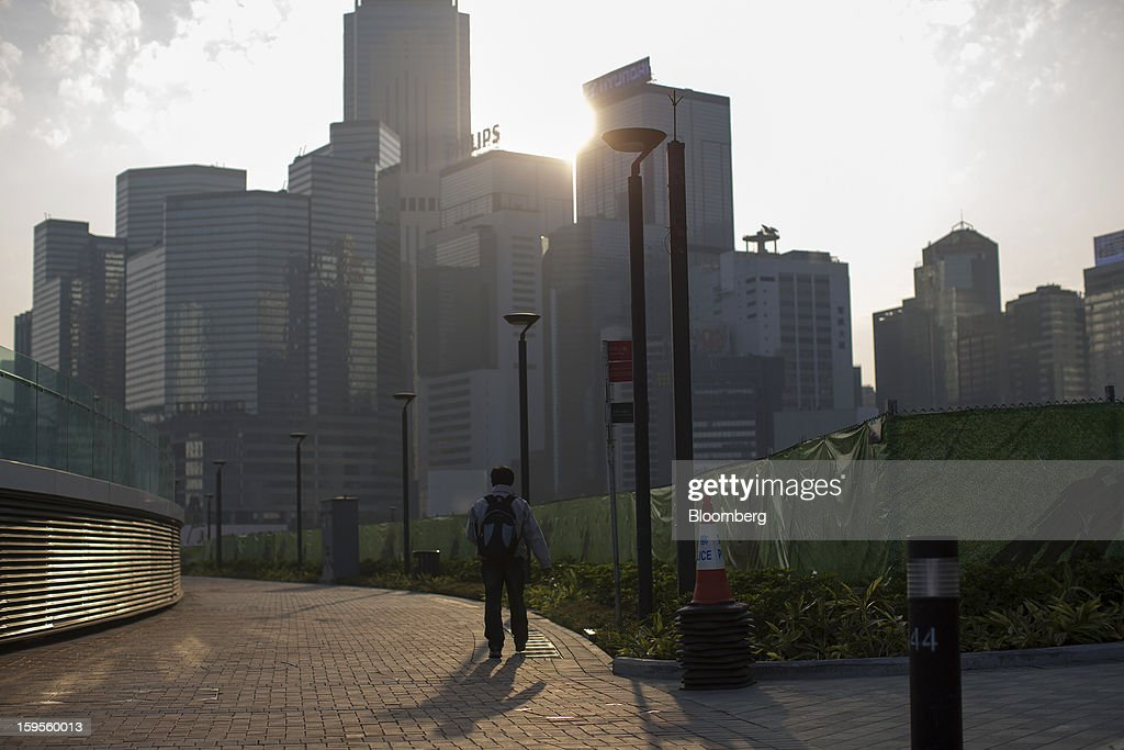 A pedestrian walks past as the sun rises over commercial buildings in the Wan Chai district in Hong Kong, China, on Wednesday, Jan. 16, 2013. Hong Kong will maintain property curbs for overseas buyers as it seeks to meet the housing needs of its people, Chief Executive Leung Chun-ying said in his first policy address today. Photographer: Jerome Favre/Bloomberg via Getty Images