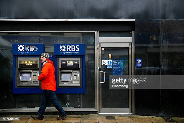 A pedestrian walks past automated teller machines outside a closed Royal Bank of Scotland Group Plc bank branch in Hove near Brighton UK on Wednesday...