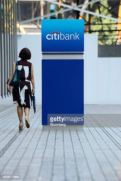 A pedestrian walks past Citibank signage displayed outside a Citigroup Inc Citibank branch in Tokyo Japan on Wednesday Aug 20 2014 Citigroup the firm...