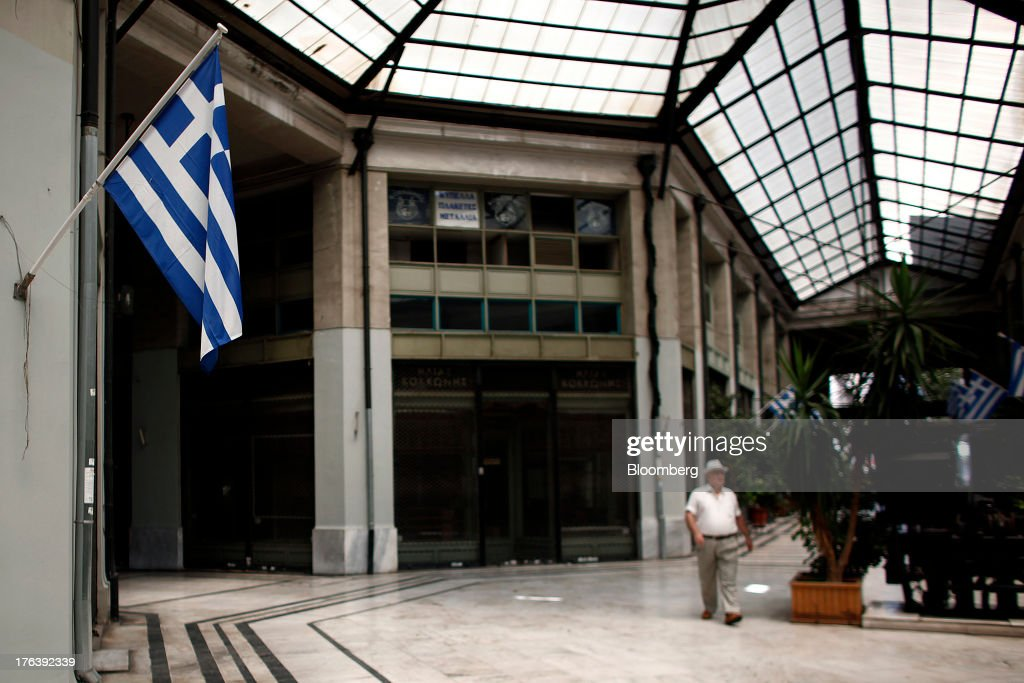A pedestrian walks past closed stores and Greek national flags in a deserted shopping mall in Athens, Greece, on Saturday, Aug. 10, 2013. Greece's economy contracted for a 20th quarter, extending an economic slump that has left more than six in 10 young Greeks out of work. Photographer: Angelos Tzortzinis/Bloomberg via Getty Images