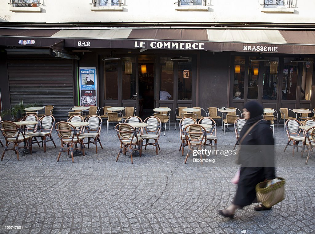 A pedestrian walks past empty tables outside the Le Commerce cafe in Paris, France, on Tuesday, Nov. 20, 2012. France's government bonds fell, with 10-year yields rising the most in a month, after Moody's Investors Service lowered the nation's top credit rating, citing a worsening economic growth outlook. Photographer: Balint Porneczi/Bloomberg via Getty Images