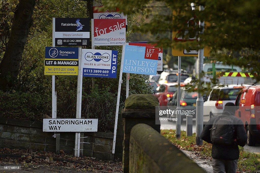 A pedestrian walks past estate agents 'for sale', 'to let' and 'let by' boards as they stand near residential buildings in Leeds, U.K., on Tuesday, Nov. 12, 2013. Under Bank of England Governor Mark Carney's forward-guidance policy, the central bank has pledged to not to withdraw stimulus at least until unemployment falls to 7 percent. Photographer: Nigel Roddis/Bloomberg via Getty Images