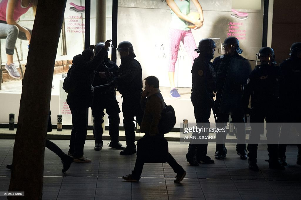 A pedestrian walks past French riot police as they ready to clear the Place de la Republique in Paris during a protest by the Nuit Debout, or 'Up All Night' movement who have been rallying against the French government's proposed labour reforms on April 29, 2016. People were arrested and others detained during the overnight clashes in the French capital as the police dispersed the protesters whose movement began on March 31 in opposition to the government's proposed labour reforms. / AFP / ALAIN