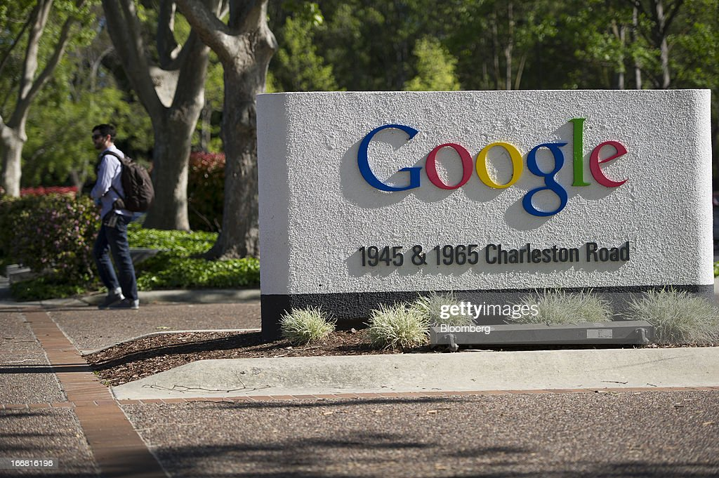 A pedestrian walks past Google Inc. signage displayed outside of the company's headquarters in Mountain View, California, U.S., on Tuesday, April 16, 2013. Google Inc. is expected to release earnings data on April 18. Photographer: David Paul Morris/Bloomberg via Getty Images