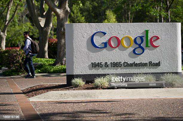 A pedestrian walks past Google Inc signage displayed outside of the company's headquarters in Mountain View California US on Tuesday April 16 2013...