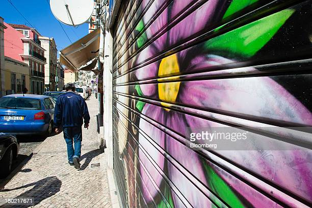 A pedestrian walks past graffiti artwork decorating the shutters of a closed store in Lisbon Portugal on Monday Sept 9 2013 Prime Minister Pedro...