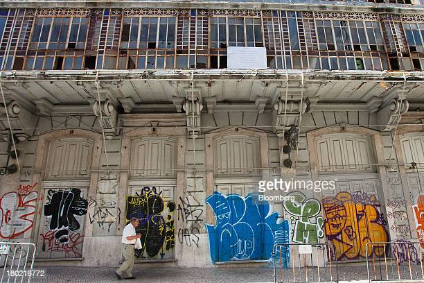 A pedestrian walks past graffiti daubed on the facade of an old building in Lisbon Portugal on Monday Sept 9 2013 Prime Minister Pedro Passos Coelho...