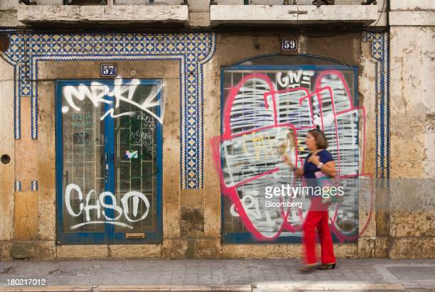 A pedestrian walks past graffiti on a shop front in Lisbon Portugal on Monday Sept 9 2013 Prime Minister Pedro Passos Coelho is poised to propose a...