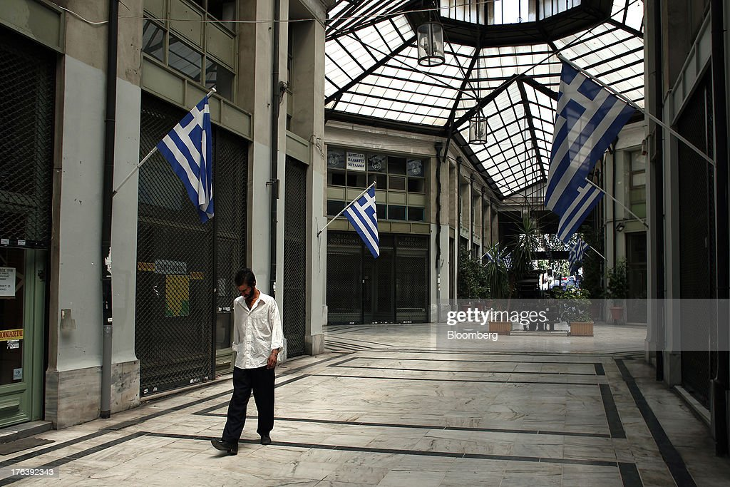 A pedestrian walks past Greek national flags hanging outside closed stores in an empty shopping mall in Athens, Greece, on Saturday, Aug. 10, 2013. Greece's economy contracted for a 20th quarter, extending an economic slump that has left more than six in 10 young Greeks out of work. Photographer: Angelos Tzortzinis/Bloomberg via Getty Images
