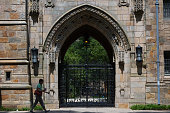 A pedestrian walks past Harkness Gate on the Yale University campus in New Haven Connecticut US on Friday June 12 2015 Yale University is an...