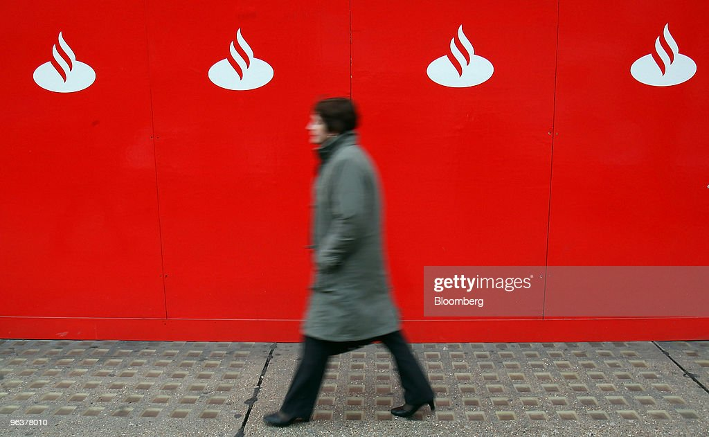 A pedestrian walks past hoarding in front of a branch of Banco Santander ATM in London, U.K., on Wednesday, Feb. 3, 2010. Banco Santander announce FY earnings tomorrow. Photographer: Simon Dawson/Bloomberg via Getty Images