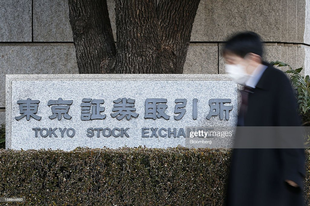 A pedestrian walks past Japan Exchange Group Inc.'s Tokyo Stock Exchange (TSE) on the first trading day of the year in Tokyo, Japan, on Friday, Jan. 4, 2013. Japan Exchange, created by the merger of Japan's two biggest bourses, fell in its trading debut on the Tokyo Stock Exchange. Photographer: Kiyoshi Ota/Bloomberg via Getty Images