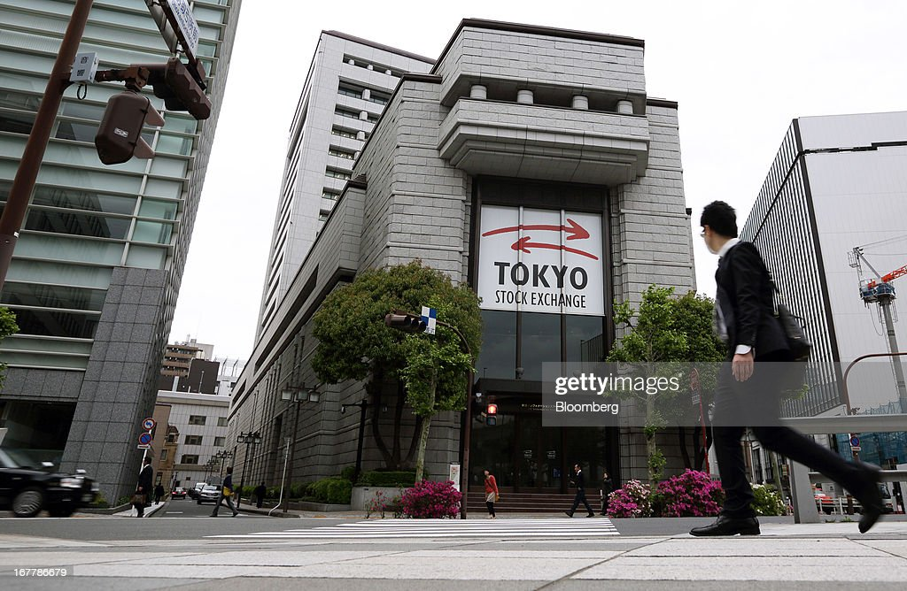 A pedestrian walks past Japan Exchange Group Inc.'s Tokyo Stock Exchange in Tokyo, Japan, on Tuesday, April 30, 2013. Japan Exchange Group Inc. forecast full-year profit that was almost half of analyst estimates in its first annual earnings report after the merger of the Tokyo Stock Exchange Group Inc. and Osaka Securities Exchange Co. Photographer: Tomohiro Ohsumi/Bloomberg via Getty Images