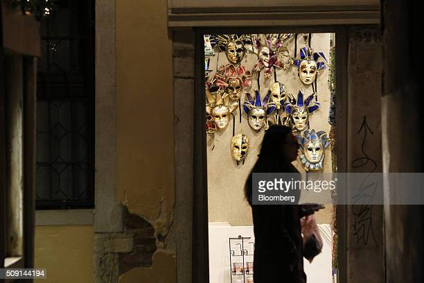 A pedestrian walks past masks hanging on display inside a store during the 2016 Carnevale di Venezia in Venice Italy on Friday Feb 5 2016 The annual...