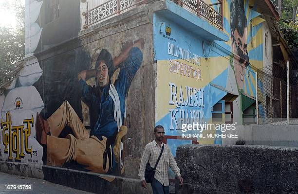A pedestrian walks past murals of Indian Bollywood actors Amitabh Bachchan and the late Rajesh Khanna in Mumbai on May 3 2013 India's movie industry...