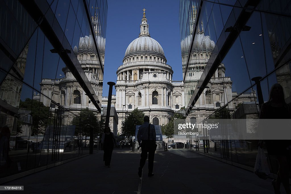 A pedestrian walks past office buildings near St. Paul's Cathedral in London, U.K., on Monday, July 8, 2013. Britain's economy could be in line for a period of 'strong catch-up growth' once it gets through the current weakness, according to Capital Economics Ltd. Photographer: Simon Dawson/Bloomberg via Getty Images