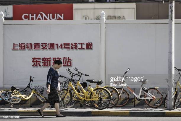 A pedestrian walks past Ofo Inc and Beijing Mobike Technology Co bicycles on a sidewalk in Shanghai China on Thursday Sept 12 2017 Across Chinese...