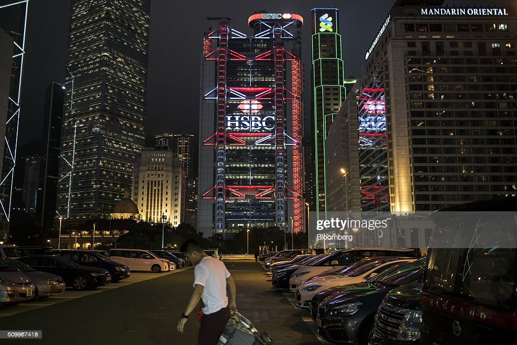 A pedestrian walks past parked cars below the HSBC Holdings Plc headquarters, center, the Standard Chartered Bank building and Mandarin Oriental Hotel, right, at night in Hong Kong, China, on Saturday, Feb. 13, 2016. HSBC's board will meet on Sunday to decide whether to shift its headquarters from London, according to two people with knowledge of the decision. Photographer: Xaume Olleros/Bloomberg via Getty Images