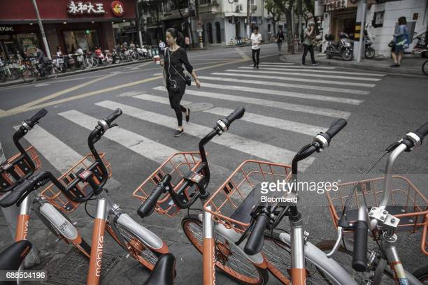 A pedestrian walks past parked Mobike bicycles on a sidewalk in Shanghai China on Thursday May 25 2017 In China a bicyclesharing phenomenon is...