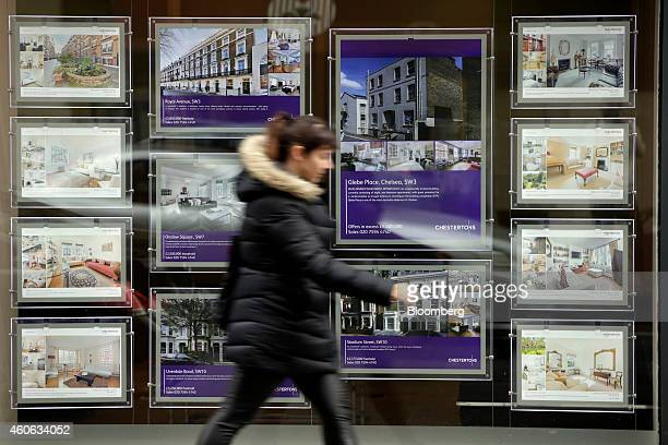 A pedestrian walks past property information leaflets displayed in the window of an estate agent in the Chelsea district of London UK on Wednesday...