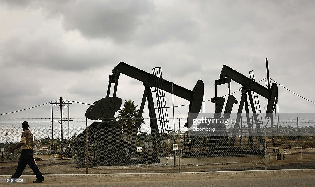 A pedestrian walks past pumpjacks operating at the Inglewood Oil field in Los Angeles, California, U.S., on Thursday, Oct. 19, 2012. The Inglewood Oil Field is a steady source of domestic oil and natural gas as well as the second most productive oil field in the entire L.A. Basin. Photographer: Patrick T. Fallon/Bloomberg via Getty Images