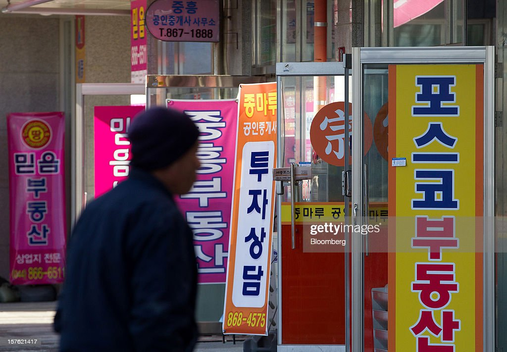 A pedestrian walks past real estate agencies in Sejong, South Korea, on Tuesday, Dec. 4, 2012. The construction of Sejong City 120 kilometers (75 miles) south of the capital fulfills the vision of the late President Roh Moo Hyun, who pledged to reduce the dominance of Seoul and pump money into a region courted for its swing voters. Photographer: SeongJoon Cho/Bloomberg via Getty Images