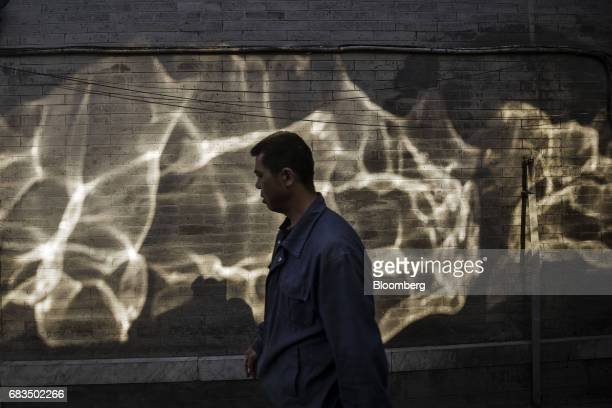 A pedestrian walks past reflections of light falling on a wall in a traditional hutong neighborhood in Beijing China on Sunday May 14 2017 Chinas...