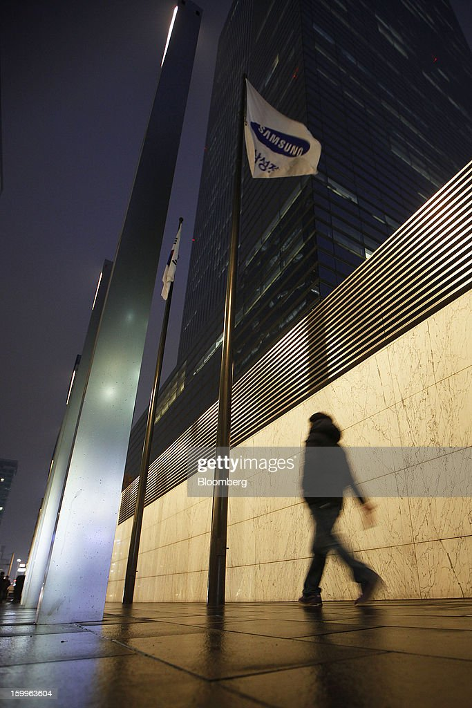 A pedestrian walks past Samsung Electronics Co.'s offices as the company's corporate flag flies in Seoul, South Korea on Wednesday, Jan. 23, 2013. Samsung, in a preliminary statement of results on Jan. 8, reported an 89 percent jump in profit in the three months ended in December, boosted by its Galaxy line of smartphones. Photographer: Woohae Cho/Bloomberg via Getty Images
