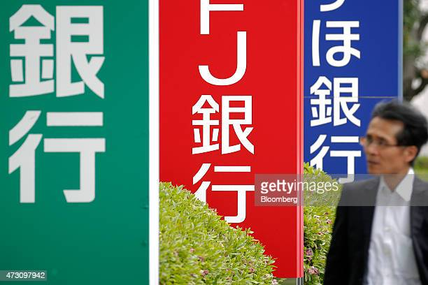 A pedestrian walks past signage for Mizuho Bank Ltd right Bank of Tokyo Mitsubishi UFJ Ltd center and Resona Bank Ltd in Tokyo Japan on Tuesday May...