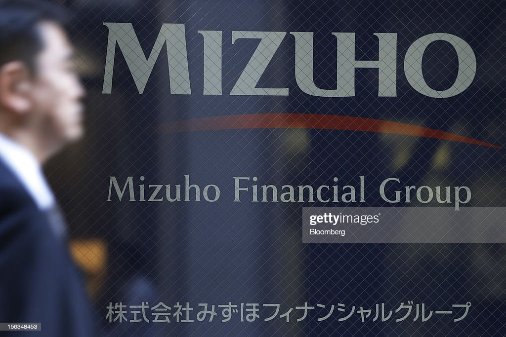 A pedestrian walks past signage for Mizuho Financial Group Inc. outside the company's headquarters in Tokyo, Japan, on Tuesday, Nov. 13, 2012. Mizuho Financial Group Inc. is scheduled to announce first-half earnings results on Nov. 14. Photographer: Kiyoshi Ota/Bloomberg via Getty Images
