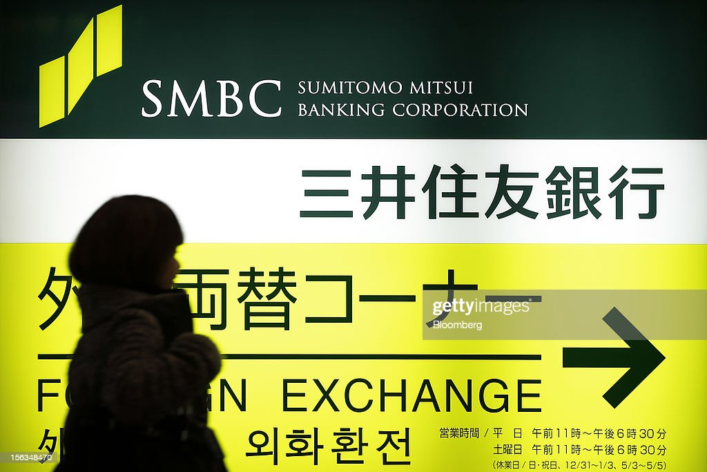 A pedestrian walks past signage for Sumitomo Mitsui Banking Corp. outside a branch in Tokyo, Japan, on Tuesday, Nov. 13, 2012. Sumitomo Mitsui Financial Group Inc. is scheduled to announce first-half earnings results on Nov. 14. Photographer: Kiyoshi Ota/Bloomberg via Getty Images