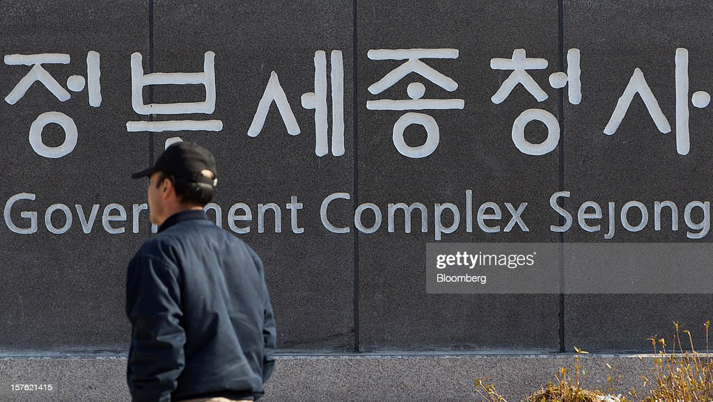 A pedestrian walks past signage for the Government Complex in Sejong, South Korea, on Tuesday, Dec. 4, 2012. The construction of Sejong City 120 kilometers (75 miles) south of the capital fulfills the vision of the late President Roh Moo Hyun, who pledged to reduce the dominance of Seoul and pump money into a region courted for its swing voters. Photographer: SeongJoon Cho/Bloomberg via Getty Images