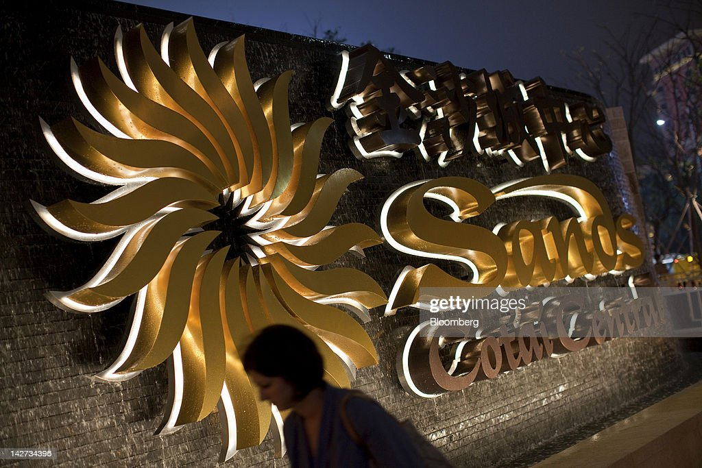 A pedestrian walks past signage for the Sands Cotai Central casino resort in Macau, China, on Wednesday, April 11, 2012. Las Vegas Sands Corp. Chairman Sheldon Adelson plans to spend $35 billion on building Spanish gambling resorts over nine years and will add a new Macau location to expand globally. Photographer: Jerome Favre/Bloomberg via Getty Images
