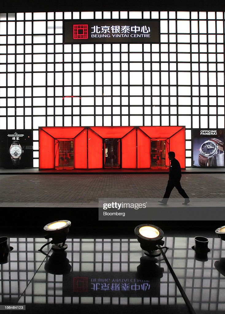 A pedestrian walks past stores at the Beijing Yintai Centre in Beijing, China, on Monday, Nov. 12, 2012. China's retail sales exceeded forecasts and inflation unexpectedly cooled to the slowest pace in 33 months, signaling the government is boosting growth without driving a rebound in prices. Photographer: Tomohiro Ohsumi/Bloomberg via Getty Images
