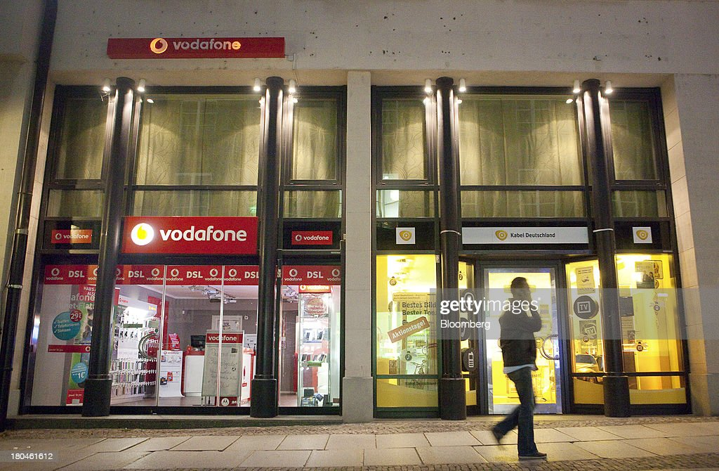 A pedestrian walks past stores for Vodafone Group Plc, left, and Kabel Deutschland Holding AG as they sit side by side in Leipzig, Germany, on Thursday, Sept. 12, 2013. Vodafone Group Plc's 7.7 billion-euro ($10.2 billion) bid for Kabel Deutschland Holding AG cleared a major hurdle by winning the backing of at least 75 percent of the German company's shareholders. Photographer: Krisztian Bocsi/Bloomberg via Getty Images
