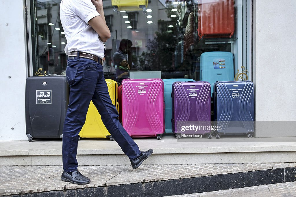 A pedestrian walks past suitcases displayed outside a store window in the suburb of Bandra in Mumbai, India, on Saturday, July 6, 2013. India's consumer price index (CPI) figures for June are scheduled to be released on July 12. Photographer: Dhiraj Singh/Bloomberg via Getty Images