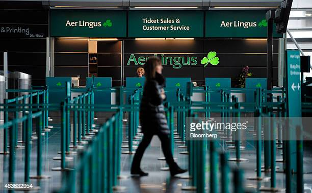 A pedestrian walks past the Aer Lingus Group Plc ticket and customer services desk in the departure hall at Dublin Airport operated by Dublin Airport...